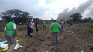 Rescatistas cerca de los restos humeantes del avión en México.