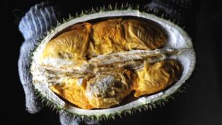 A vendor displays the cross section of a durian fruit at a roadside shop in Karak