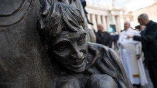 """A close up of one of the migrants depicted in the """"Angels Unaware"""" boat"""