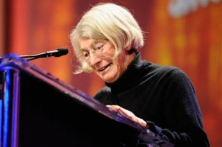 Poet Mary Oliver speaks from a lectern, pictured in October 2010 in Long Beach, California
