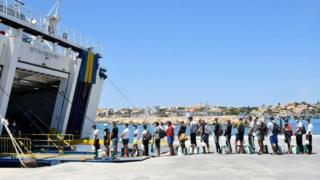 Migrants escorted by police queue to board on a tourists ferry boat to Porto Empedocle onthe Italian island of Lampedusa on 29 July 2020
