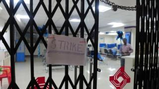 "A ""strike"" placard is fixed onto the padlocked gate of a public sector bank during a nationwide strike called by 10 major trade unions over wages and economic reforms, in Chennai on September 2, 2016."
