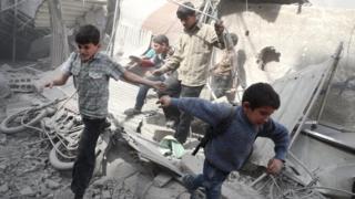 Niños huyen de una explosión en Siria