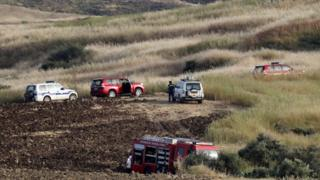 Police and rescue vehicles have been investigating the grassy, hilly area where one of the bodies was found near the village of Orounta in Cyprus