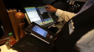 Waitress Courtney Jones processes a dinner tab with a Rail table side credit card processing device at Tableau,