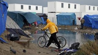 A migrant walks among tents in a makeshift camp in Calais, France. File photo