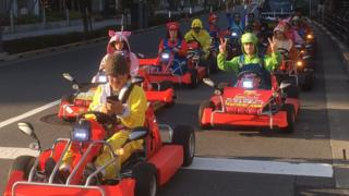 Drivers in Super Mario cosplay outfits drive kart on Tokyo public roads