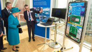 Alex Dewdney (right) gives the Queen a demonstration of how an electricity supply could be subjected to cyber attack