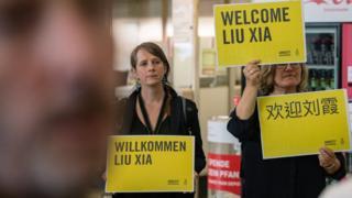 刘霞到达德国柏林时,有民间组织人士到机场举起标语欢迎。