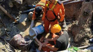 Rescuers try to pull out a woman trapped in the rubble in Palu. Photo: 30 September 2018