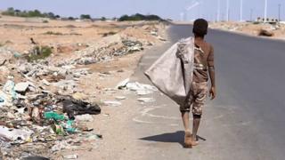 เด็กแบกถุงอยู่ข้างถนน