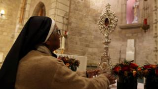 A worshipper looks at a fragment of a wooden relic, reputed to be from Jesus' manger, in Jerusalem, 29 November, 2019.