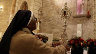 راهبة تحمل قطعة من مهد المسيح في القدس قبل رحلة عودتها إلى بيت لحم