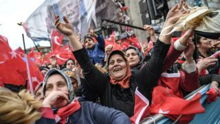 Supporters of Justice and development Party (AKP) cheer and wave Turkish national flags as Turkish President speaks