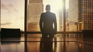 Silhouette of businessman looking out at financial district