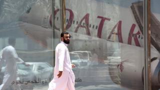 Hombre caminando frente a un reflejo de un avión de la línea aérea de Qatar