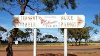 A road sign pointing directions to Tennant Creek and Alice Springs