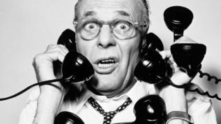 Un hombre atendiendo muchos teléfonos, en una fotografía en blanco y negro