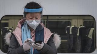 Maskeli bir gezgin Wuhan'daki Hankou Tren İstasyonu'ndaki platformda telefonuna bir mesaj gönderir