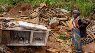 Umukecuru ahagaze impande y'inzu yiwe yasambuwe n'igihuhusi muri Mozambique, itariki 19/03/2019