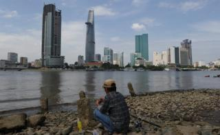 Ho Chi Minh City skyline with man fishing in foreground