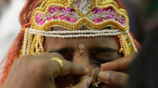 An Indian bride grimaces as a relative adjusts her nose ring during a multi-faith mass wedding in Mumbai on June 22, 2014.