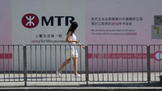 一位女土在港鐵紅磡站改建工程的圍板前走過(BBC News中文圖片9/8/2018)