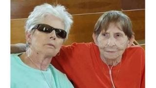 Two women sit side by side