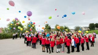 Pupils releasing balloons