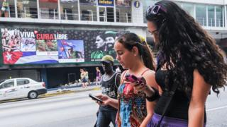 Cubanas usan su celular en La Habana.