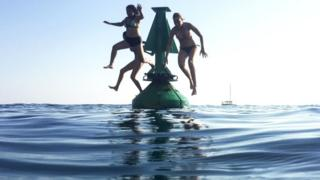 Swimmers jump off a buoy into the sea in Nice, south-eastern France, on 6 August 2018,