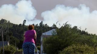 A woman looks on as forest fires tear through Gran Canaria