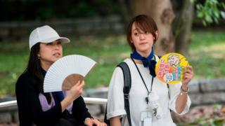 People in Tokyo fan themselves