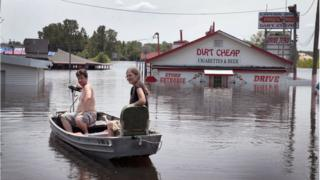 Penduduk Missouri pulang ke rumah dengan menggunakan perahu sementara banjir terus meningkat dari sungai Mississippi