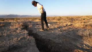 A local resident inspects a crack in the earth