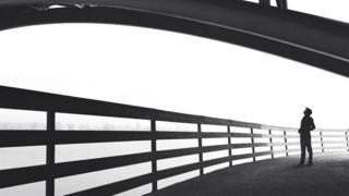 Una persona, a contraluz, caminando por un puente, y mirando a su alrededor, como perdida