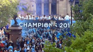 Manchester City players on a open-top bus