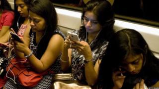મેટ્રો ટ્રેનમાં મોબાઇલ ફોન વાપરતી છોકરીઓ
