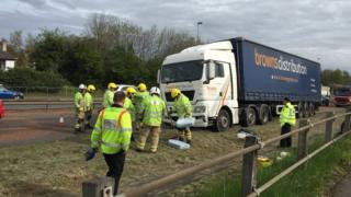 Firefighters clean up a diesel spill following a lorry crash - around 6 or 7 fighfighters are pictured in high vis clothing
