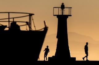 The silhouettes of joggers are seen next to a lighthouse and a boat at sunrise.