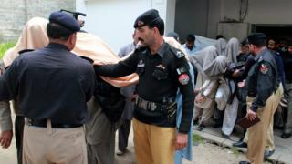 Police lead away arrested members of the jirga outside a court in Abbottabad, Pakistan. 5 May 2016