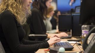 Young female intern working at office computer