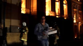 Mujer rescatando objetos del interior del Museo.