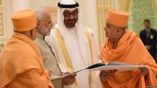 अबू धाबी में मंदिर कमिटी के सदस्य पीएम मोदी और अबू धाबी के क्राउन प्रिंस को मंदिर की बुकलेट दिखाते हुए