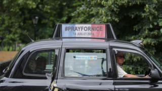 "A London taxi carries a sign ""Pray for Nice"""