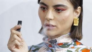 A model smokes a vape before the Snow Xue Gao Spring Summer 2018 show during New York Fashion Week on 8 September 2017 in New York