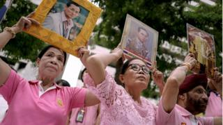 Well-wishers hold pictures of Thailand's King Bhumibol Adulyadej as they pray for him at the Siriraj hospital where he is residing in Bangkok, 12 October 2016