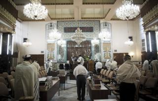 Iranian Jewish men wearing Tallit shawls and read from the Torah during morning prayers at Youssef Abad synagogue in Tehran on September 30, 2013. Present for more than 2,500 years in Persia, Iranian Jews have lost more than 70 percent of their 80,000 to 100,00 population who lived in Iran prior to the 1979 Islamic revolution, today Iran is home to some 8,750 Jews, according to a 2011 census. They are scattered across the country, but are mostly in the capital Tehran, Isfahan in the center, and Shiraz in the south. AFP PHOTO/BEHROUZ MEHRI (Photo credit should read BEHROUZ MEHRI/AFP/Getty Images)