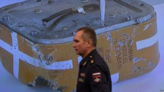 A Russian military official passes by a screen showing a live broadcast of the opening of the flight recorder from the Russian Su-24 bomber in Moscow, 18 December