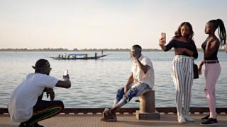 Malians take pictures of each other on the banks of River Niger in Segou, Senegal - Saturday 8 February 2020